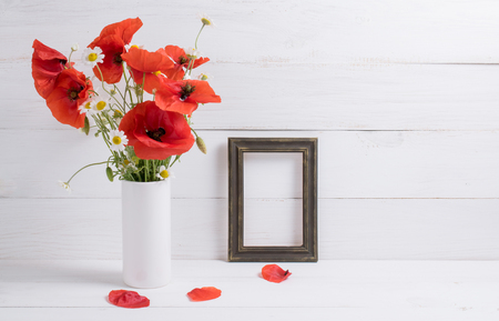 Red poppies bouquet in vase and photo frame on background of white wooden planks in scandinavian style Stock Photo