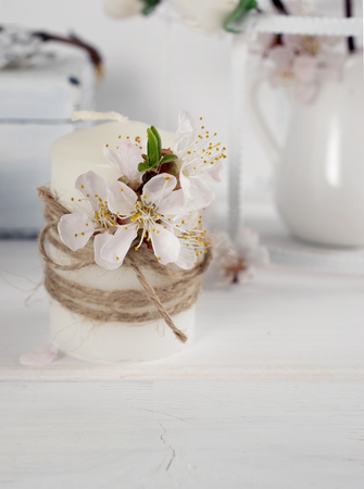 Candle with apricot flowers. Spring interior.