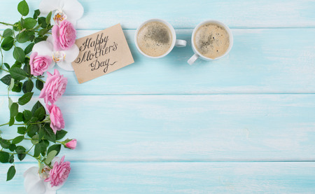 Pink roses with coffee cups and paper greeting card for Mothers day on background of shabby wooden planks. Copy space. Top view. Flat design. Фото со стока