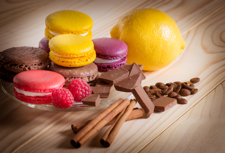 lemony: Macaroon with  chocolate, raspberry, cinnamon and lemon on the wooden table. For this photo applied vignetting effect. Stock Photo
