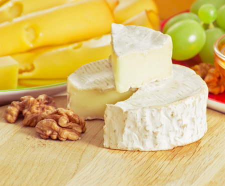 tabla de quesos: Round camembert cheese with smoked cheese, walnuts and grapes on the wooden board