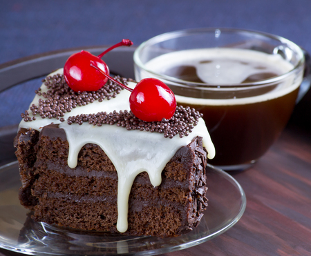 Celebratory chocolate cake with canned cherry, cup of coffee on the wooden tray.