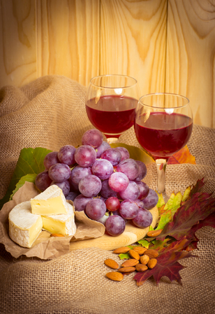 tabla de quesos: Red wine with cheese, almonds and grapes on sackcloth on a background of a wooden wall and autumn leaves. For this photo applied vignetting effect. Foto de archivo