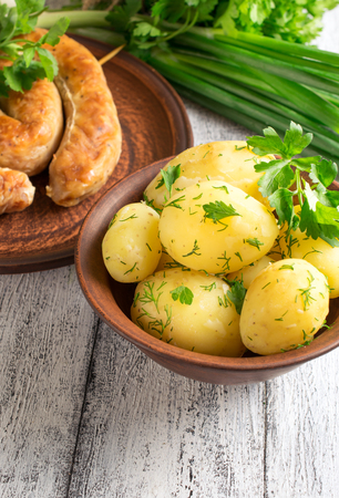 veal sausage: Young boiled potatoes with dill in the bowl, sausage on the plate, parsley and onions on the wooden board