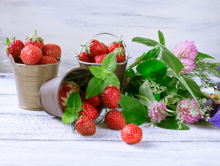 Strawberry in a small bucket and flowers on the wooden board.  Stock Photo