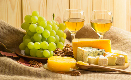 stilton: White wine with blue cheese, camembert and swiss cheese, walnuts, honey and grapes on sackcloth on a background of a wooden wall and autumn leaves