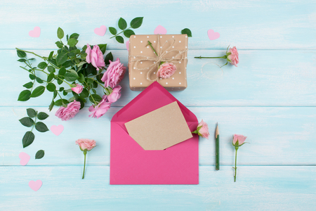 Pink roses with envelope, blank sheet paper for greeting text and gift box on background of shabby wooden planks. Copy space. Top view. Flat design. Stock Photo