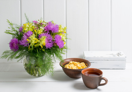 Flowers bouquet in glass round vase with cup tea and corn flakes on background of white wooden planks in provence style. Home interior.