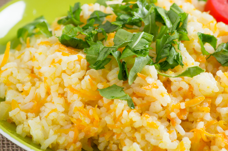Rice with carrot and fresh rucola leaves