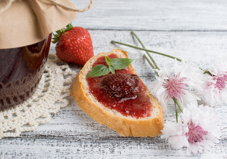 strawberry jam sandwich: Canned strawberry confiture and jam sandwich on the wooden board in rustic style