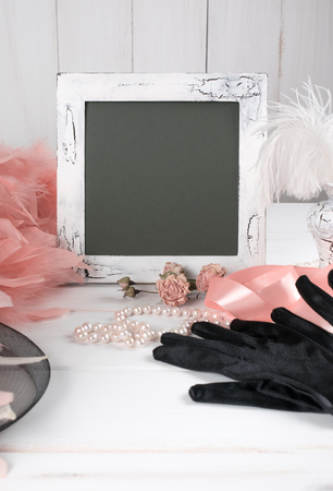 craquelure: Old photo frame and womens retro accessories including velvet gloves and pearl necklace on wooden  table