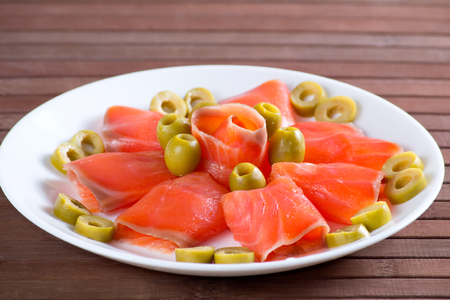 Sliced salted salmon served with olive on white plate