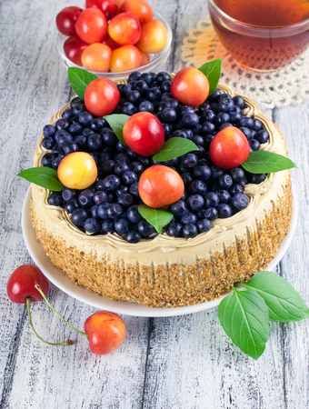 worn: Celebratory cake with blueberries, sweet cherry, mint leaves and cup tea on the shabby board in rustic style Stock Photo