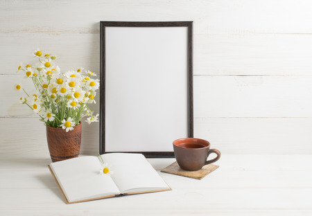 Daisy bouquet  with  motivational frame, open notebook and cup tea on background of white wooden planks in scandinavian style. Home interior. Stock Photo