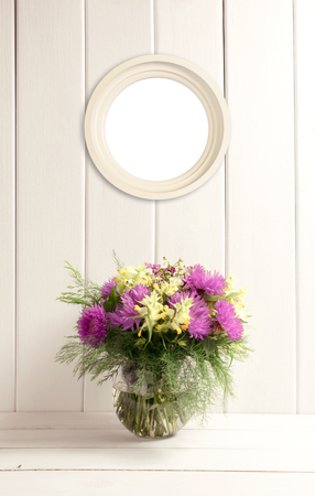 Flower bouquet in glass round vase and round frame on background of white wooden planks in provence style. Home interior. Empty place for photo or text. Copy space. Stock Photo