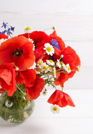 Red poppies bouquet in round vase on background of white wooden planks in scandinavian style