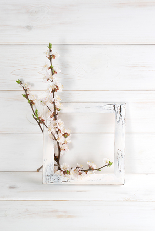 Decorated frame and apricot flowers in home interior on wooden boards in shabby chic style. Copy space.