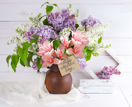 Lilac bouquet and magnolia in clay jug with congratulatory card, tulle fabric, vintage casket and retro photo frame on background of shabby wooden planks in rustic style Zdjęcie Seryjne