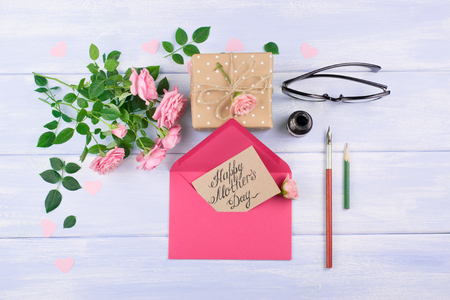 Pink roses with paper greeting card, inkwell and fountain pen, gift box for Mothers day on background of shabby wooden planks. Top view. Flat design.