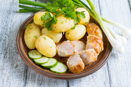 veal sausage: Young boiled potatoes with dill in the bowl, sausage and cucumber on the plate, parsley and onions on the wooden board