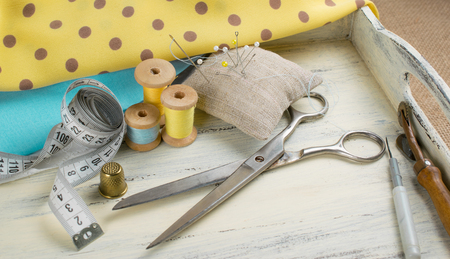 Set of reel of thread, centimeter, fabric, thimble and scissors, seam ripper, toothed wheel, needle and pins for sewing and needlework on the wooden board in Shabby Chic style.