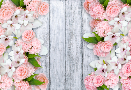 Magnolia flowers with roses, hortensia and place for your text on background of shabby wooden planks in rustic style. Top view. Flat design. Copy space.