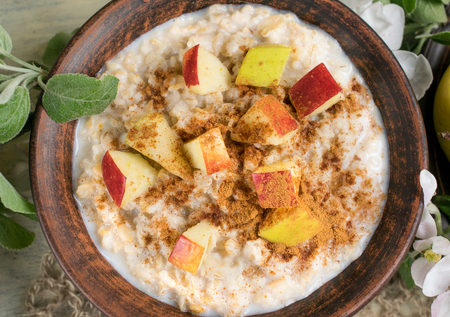 Oatmeal with apple and cinnamon in the ceramic bowl Фото со стока - 79898868