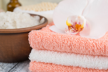 Spa salon with sea salt, towels and flowers on worn wooden boards