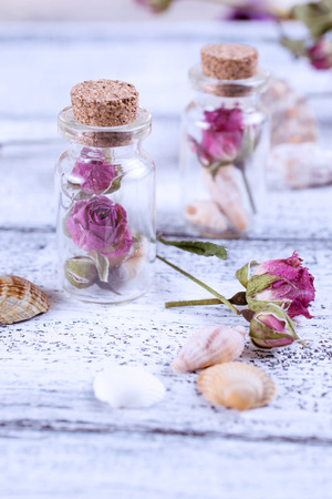 Small glass bottle filled dry roses and seashells on the worn wooden boards Stock Photo