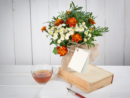 sheet of paper: Tagetes flower bouquet with decorative greeting card and old book with cup tea and nib pen on white wooden boards in shabby chic style Stock Photo