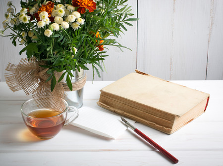 nib: Tagetes flower bouquet with old book and cup tea and nib pen on white wooden boards in shabby chic style