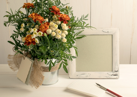 sheet of paper: Retro photo frame and old pen with sheet paper and tagetes bouquet on wooden board in shabby chic style