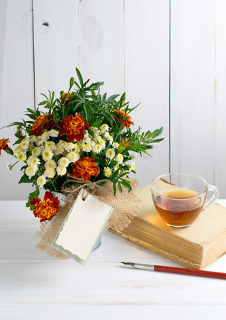Tagetes flower bouquet with decorative greeting card and old book with cup tea and nib pen on white wooden boards in shabby chic style Stock Photo