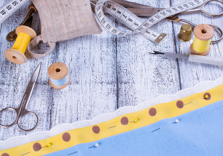 Tools for sewing and fabric on wooden boards  in Shabby Chic style.