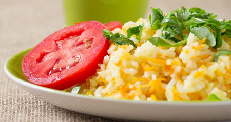 Rice with carrot, tomatoes  and fresh rucola leaves