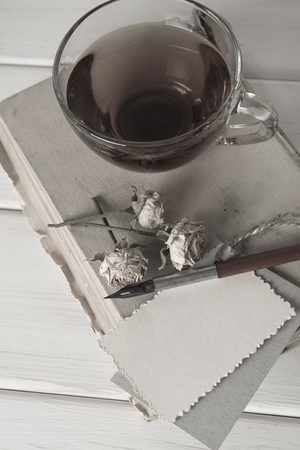 nib: Old book with decorative greeting card, dried roses, nib pen and cup tea on white wooden boards