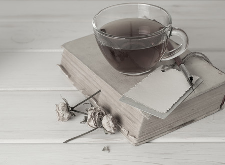 scruffy: Old book with decorative greeting card, dried roses, nib pen and cup tea on white wooden boards