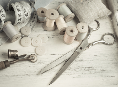 pin board: Set of reel of thread, scissors, buttons, fabric and pins for sewing and needlework in Shabby Chic style. For this photo applied toning in retro style.