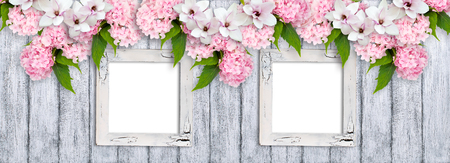 Wooden background and photo frames with pink magnolia flowers, roses and hortensia in rustic style