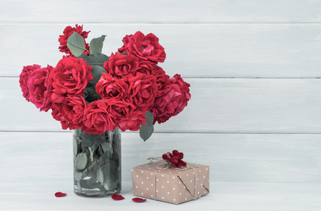 Roses bouquet and gifts on wooden background in Shabby Chic style. Celebratory interior. Empty place for text. Stock Photo