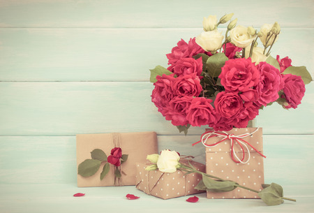 Roses bouquet and gifts on wooden background in Shabby Chic style. Celebratory interior. Empty place for text. For this photo applied toning effect and vignetting.