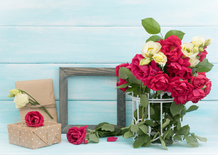 Roses in birdcage, vintage photo frame and gifts in Shabby Chic style. Celebratory interior.