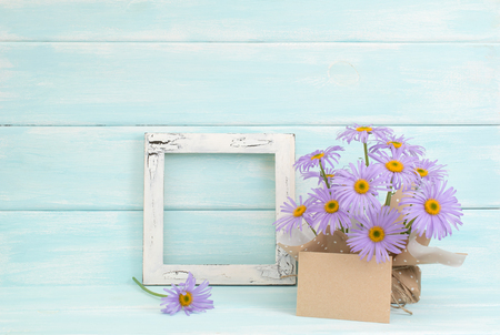 Chamomile, empty paper and vintage photo frame  on wooden background in Shabby Chic style. Celebratory interior. Place for text.