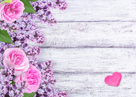 Lilac flowers with wild roses and heart on shabby wooden planks. Roses background.