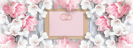 Magnolia and bridal rings with paper greeting card for wedding on background of shabby wooden planks. Copy space. Top view. Flat design.