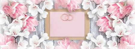 Magnolie und Brautringe mit Papiergrußkarte für die Heirat auf Hintergrund von schäbigen hölzernen Planken. Kopieren Sie Platz. Draufsicht. Flaches Design.
