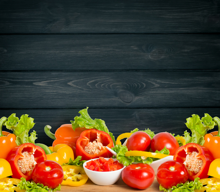 Ripe bell peppers, lettuce and tomato on dark wooden board and empty place for text. Heap of various fresh bio vegetables. Healthy eating theme. Copy space.