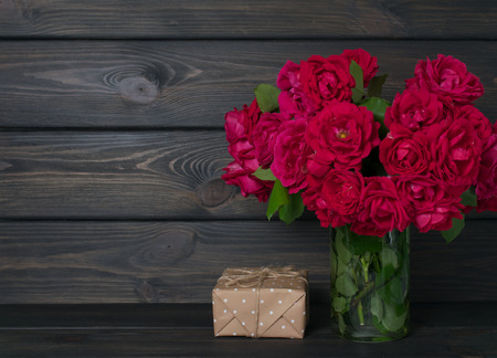 Roses bouquet and gift box on wooden background in rustic style. Celebratory interior. Empty place for text. Stock Photo