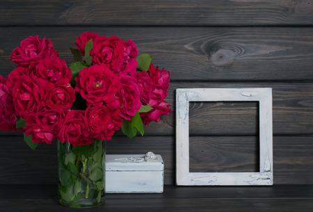 Roses in vase and and vintage photo frame on background of wooden planks in rustic style. Celebratory interior.