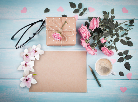 Pink roses with blank paper sheet and magnolia flowers for greeting text and gift box, coffee cup on background of shabby wooden planks. Copy space. Top view. Flat design.